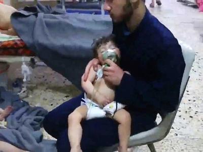 Une image prise sur une vidéo de la Défense civile syrienne montre des volontaires aidant des enfants victimes d'une attaque chimique présumée à Douma, le 8 avril 2018 - HO [AFP]