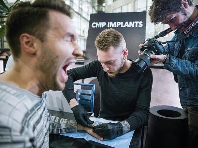 Un homme réagit alors qu'un autre insère un implant sous sa peau, à Stockholm, le 18 janvier 2018    Jonathan NACKSTRAND [AFP]