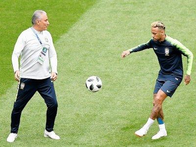 L'entraîneur du Brésil Tite (g) donne des instructions à son joueur vedette Neymar lors d'un enttraînement au stade de Saint-Pétersbourg, le 21 juin 2018    GABRIEL BOUYS [AFP]