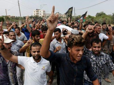 Photo prise le 14 juillet 2018 à Khan Younès, dans le sud de la bande de Gaza, montrant des Palestiniens portant la dépouille de Mohamad Nassir Shurab, décédé de ses blessures après avoir été blessé par balles par les forces israéliennes vendredi lor    SAID KHATIB [AFP]