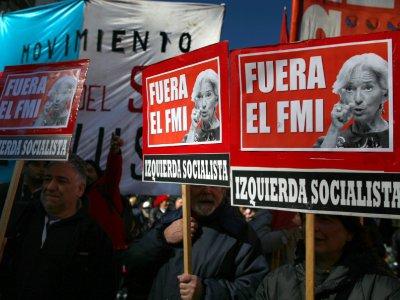 """Des manifestants brandissent des pancartes """"FMI dehors"""" lors du G20, le 21 juillet 2018 à Buenos Aires, en Argentine    AGUSTIN MARCARIAN [AFP]"""