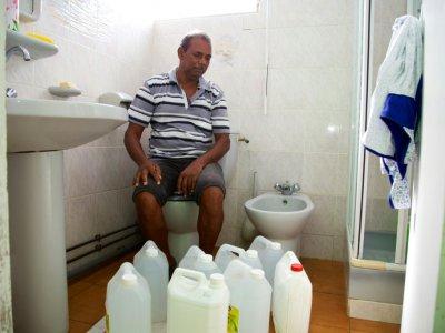 Un habitant pose avec ses bidons utilisés pour stocker l'eau dans sa salle de bain à Capesterre, en Guadeloupe, le 26 juillet 2018    Cedrick Isham CALVADOS [AFP]