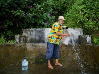 Un homme remplit des bonbonnes d'eau de source à Trois-Rivières, en Guadeloupe, le 26 juillet 2018    Cedrick Isham CALVADOS [AFP]