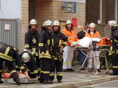 Des secouristes prennent soin des personnes blessées le 27 juillet 2000 lors d'un attentat raciste à Düsseldorf (Allemagne) dont le seul suspect a été acquitté - Christian OHLIG [dpa/AFP]