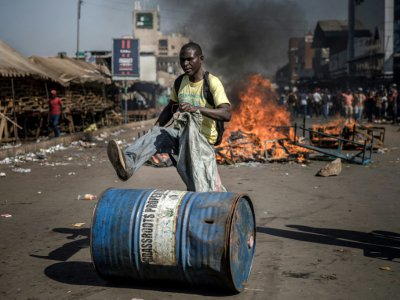 Un partisan de l'opposition au Zimbabwe pousse un bidon devant une barricade enflammée, le 1er août 2018 à Harare. - Luis TATO [AFP]