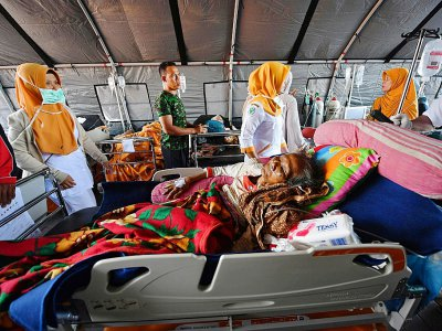 Des équipes de secours prennent en charge des blessés dans un hôpital de fortune, le 6 août 2018 à Mataram, après un séisme meurtrier sur l'île de Lombok, en Indonésie - ADEK BERRY [AFP]