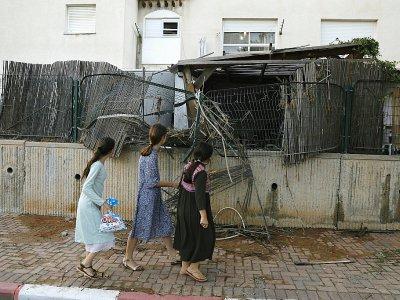 Des habitants de la ville de Sdérot dans le sud d'Israël passent devant une clôture endommagée par la chute d'une roquette tirée de la bande de Gaza, le 14 juillet 2018 - Ahmad GHARABLI [AFP]