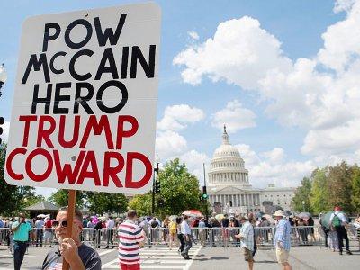 Un militant anti-Trump devant le Capitole, où des centaines de personnes faisaient la queue, le 31 août 2018, à Washington, pour rendre un dernier hommage à John McCain    SAUL LOEB [AFP]