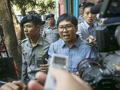 Le journaliste birman Wa Lone (c) escorté par des policiers après son procès à Rangoun, le 4 avril 2018    SAI AUNG MAIN [AFP/Archives]