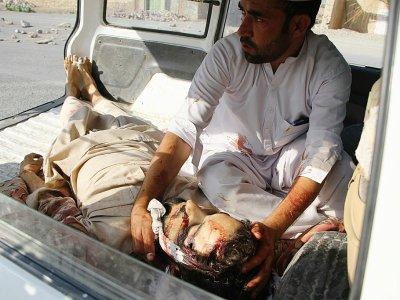 Un homme tient la tête d'un autre homme tué dans un attentat dans l'est de l'Afghanistan, le 11 septembre 2018 - NOORULLAH SHIRZADA [AFP]