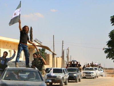 Des combattants rebelles syriens, du Front national de libération (FNL) récemment créé, défilent dans le nord de la province syrienne d'Idleb, après un entraînement militaire, le 11 septembre 2018    Aaref WATAD [AFP/Archives]