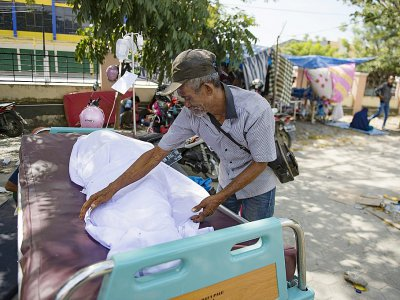 Un homme avec la dépouille de son fils le 2 octobre 2018 dans une morgue improvisée devant un hôpital de Palu, ville indonésienne frappée par un séisme et un tsunami - BAY ISMOYO [AFP]