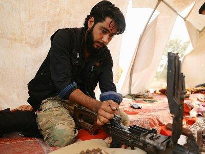Un combattant rebelle syrien du Front national de libération (FNL) s'occupe de son arme, dans le sud-est de la province d'Idleb, le 9 octobre 2018 - OMAR HAJ KADOUR [AFP]
