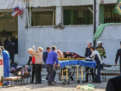 Des sauveteurs évacuent un blessé de la tuerie au lycée polytechnique de Kertch, en Crimée, le 17 octobre 2018 - - [KERCH.FM/AFP]