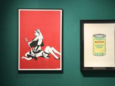 """Les œuvres """"Queen Vic"""" et """"Soup can yellow"""" réalisées par l'artiste britannique Banksy exposées à la vente chez Artcurial à Paris, le 24 octobre 2018 - JACQUES DEMARTHON [AFP]"""