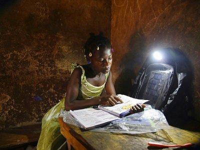 Amondji Anin Lucienne étudie à la lumière de son cartable, le 17 septembre 2018    Sia KAMBOU [AFP]