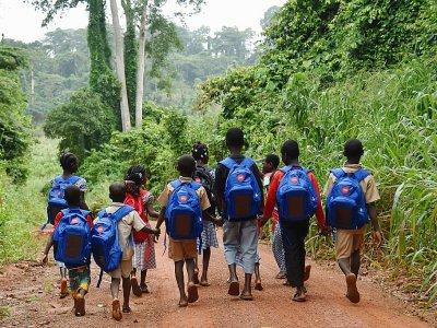 """Des écoliers sur le chemin de l'école avec leurs cartables """"solaires"""", le 17 septembre 2018 à Rubino, en Côte d'Ivoire    Sia KAMBOU [AFP]"""