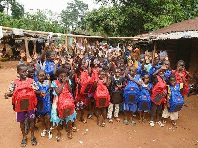 Des écoliers montrent leurs cartables solaires, le 16 septembre 2018 à Rubino, en Côte d'Ivoire    Sia KAMBOU [AFP]
