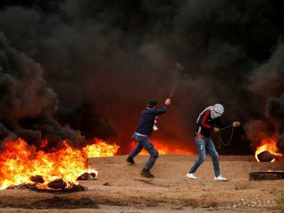 Des palestiniens lancent des pierres lors d'affrontements avec les forces de l'ordre israéliennes après une manifestation à l'est de la ville de Gaza, près de la frontière, le 26 octobre 2018    MAHMUD HAMS [AFP]