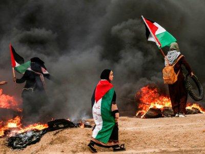 Des palestiniennes brandissent leur drapeau lors d'affrontements suite à une manifestation à l'est de Gaza, près de la frontière israélienne, le 26 octobre 2018    MAHMUD HAMS [AFP]