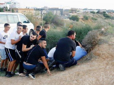 Des Israéliens se mettent à couvert à Sdérot, lors de tirs de roquettes depuis la bande de Gaza voisine, le 13 novembre 2018    JACK GUEZ [AFP]