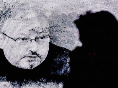 Un homme passe devant un écran projetant le portrait de Jamal Khashoggi lors d'un rassemblement en mémoire du journaliste saoudien assassiné, le 11 novembre 2018 à Istanbul - OZAN KOSE [AFP]