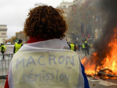 """""""Macron démission"""" peut-on lire sur ce gilet jaune, sur les Champs Elysées, le 24 novembre 2018    Bertrand GUAY [AFP]"""