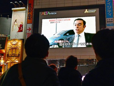 Des passants regardent le 22 novembre 2018 à Tokyo la photo de Carlos Ghosn, patron de Renault-Nissan, arrêté pour soupçons de malversations financières et fraude fiscale    Kazuhiro NOGI [AFP/Archives]