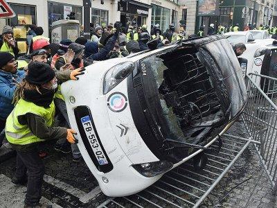 """Destruction d'une voiture pendant la manifestation des """"gilets jaunes"""" près des Champs-Elysées le 1er décembre 2018 - Lucas BARIOULET [AFP/Archives]"""