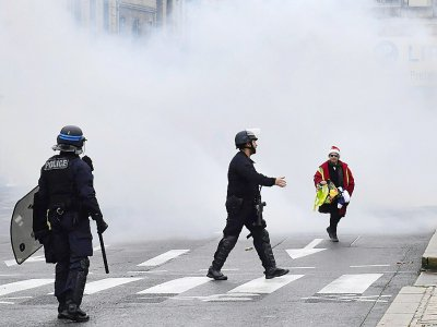 Une femme portant un bonnet de Père Noël et  un gilet jaune pendant que la police disperse une manifestation de lycéens, à Bordeaux le 3 décembre 2018 - NICOLAS TUCAT [AFP]