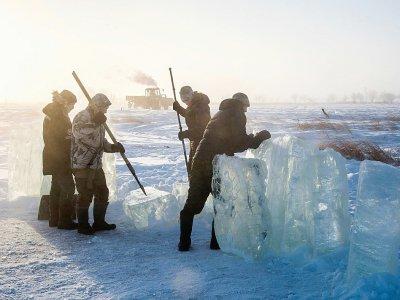 Des villageois en Iakoutie (nord-est de la Sibérie) extraient un bloc de glace qui les approvisionnera en eau douce pour l'hiver, le 27 novembre 2018 à Oï en Russie    Mladen ANTONOV [AFP]