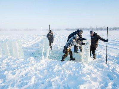 Dans le village d'Oï en Iakoutie (Russie), des villageois en quête de blocs de glace, le 27 novembre 2018    Mladen ANTONOV [AFP]