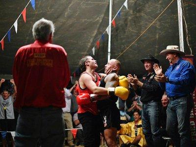 Des boxeurs se congratulent après un combat sous la tente de Fred Brophy en Australie, le 31 août 2018 - Saeed KHAN [AFP]