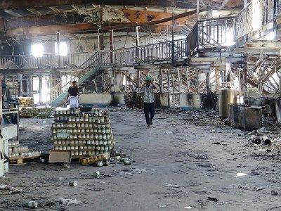 Deux hommes dans une usine détruite par les combats et les raids aériens dans la ville yéménite de Hodeida (ouest), le 17 décembre 2018    STRINGER [AFP]