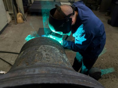 Un employé de l'entreprise Bodet effectue une soudure sur une cloche en réparation, le 17 décembre 2018 à Trémentines, dans le Maine-et-Loire en France    Sebastien SALOM-GOMIS [AFP]