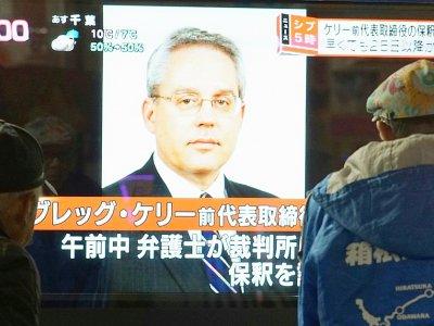 Des piétons passent devant un écran de télévision sur lequel apparaît le visage de de Greg Kelly, ancien bras droit de Carlos Ghosn, le 21 décembre 2018 à Tokyo, au Japon    Kazuhiro NOGI [AFP/Archives]