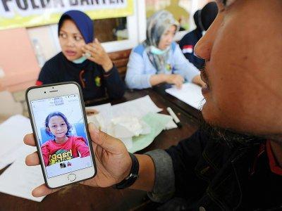 Un proche d'une victime du tsunami indonésien montre une photo à un responsable, dans le centre d'identification d'un hôpital à Pandeglang (province de Banten), le 25 décembre 2018 - SONNY TUMBELAKA [AFP]