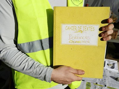 """Un """"gilet jaune"""" montre le cahier de doléances qu'il présente sur un rond-point à Cagnes-sur-mer, le 20 décembre 2018 - VALERY HACHE [AFP/Archives]"""