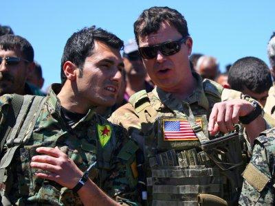 Un officier américain (à droite) parle à un combattant de la milice kurde YPG sur un site de bombardements turcs dans le nord-est de la Syrie, le 25 avril 2017    DELIL SOULEIMAN [AFP/Archives]