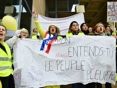 """Gilets jaunes avec la banderole """"Macron, entends-tu le peuple pleurer?"""", au Mans, le 13 janvier 2019 - JEAN-FRANCOIS MONIER [AFP]"""