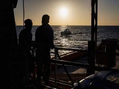 Deux migrants regardent le soleil se lever sur le pont du Sea Watch le 31 janvier 2019