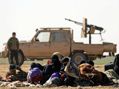 Des civils ayant fui les combats contre le groupe Etat islamique (EI) dans son ultime réduit de Syrie, et derrière eux un combattant des Forces démocratiques syriennes (SDF), près du village de Baghouz, le 3 février 2019    Delil souleiman [AFP/Archives]