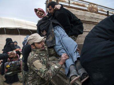 Un membre des Forces démocratiques syriennes aide des civils qui ont fui le groupe Etat islamisque à Baghouz, le 14 février 2018    Fadel SENNA [AFP]