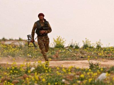 Un combattant des Forces démocratiques syriennes court avec son arme lors d'une opération contre le groupe Etat islamique, près de Baghouz en Syrie, le 14 février 2019    Delil souleiman [AFP]
