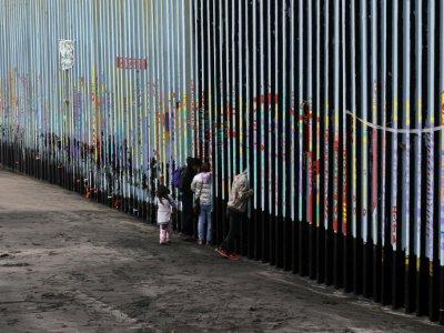 Une famille devant la barrière séparant le Mexique des Etats-Unis, le 16 janvier 2019 à Tijuana - Guillermo Arias [AFP/Archives]