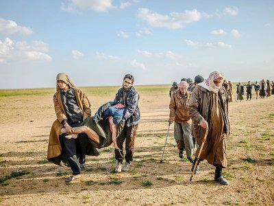 Des hommes soupçonnés d'appartenir au groupe jihadiste Etat islamique (EI) quittent le dernier réduit de l'EI en transportant un blessé le 22 février près de Baghouz dans l'est de la Syrie    Bulent KILIC [AFP]