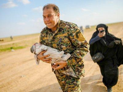 Un membre de la force antijihadiste arbo-kurde porte un bébé suivie par une femme qui vient de quitter le dernier réduit du groupe Etat islamique (EI) près de Baghouz, dans l'est de la Syrie, le 22 février 2019    Bulent KILIC [AFP]