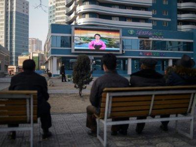 Des Nord-Corénes, assis sur un banc dans une rue de Pyongyang le 1er mars 2019, regardent sur un écran géant la speakrine officielle donner des informations sur la rencontre entre le président américain Donald Trump et leur leader Kim Jong Un à Hanoï - KIM WON JIN [AFP]