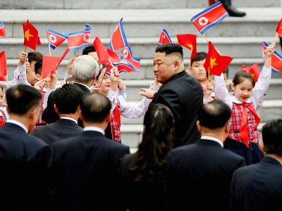 Le dirigeant nord-coréen Kim Jong Un (D) et le président vietnamien Nguyen Phu Trong (G) salués par des enfants lors d'une cérémonie d'accueil au palais présidentiel à Hanoï, le 1er mars 2019 - LUONG THAI LINH [POOL/AFP]