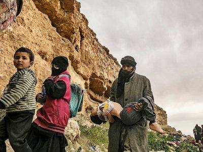 Un homme avance en tenant dans ses bras tendus devant lui un enfant immobile après être sorti du dernier réduit du groupe Etat islamique en Syrie, le 14 mars 2019    Delil souleiman [AFP]